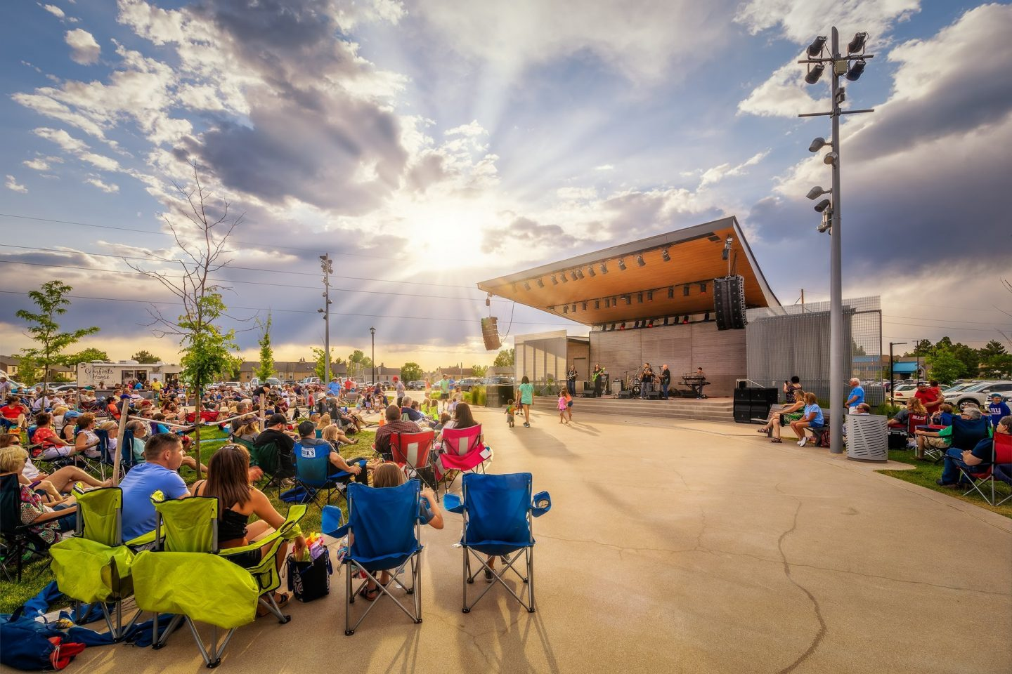 Crowd in chairs surrounding stage during performance at Discovery Park in Parker, CO.