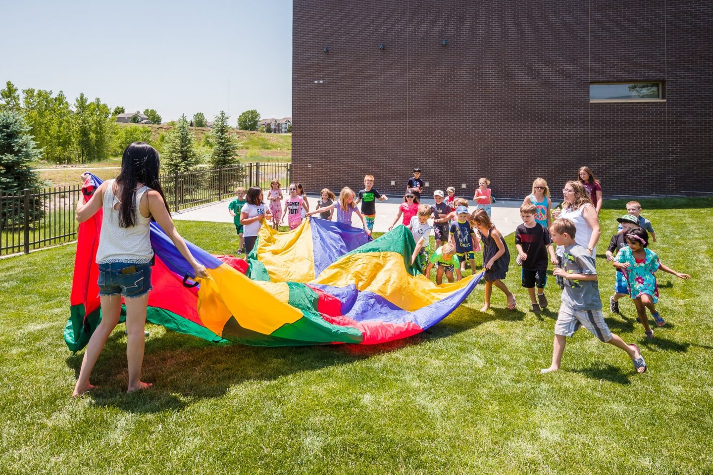 Kids playing with parachute outside of the PACE Center in Parker, CO.