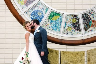 Happy wedding couple kissing in front of PACE Center outdoor art in Parker, CO.