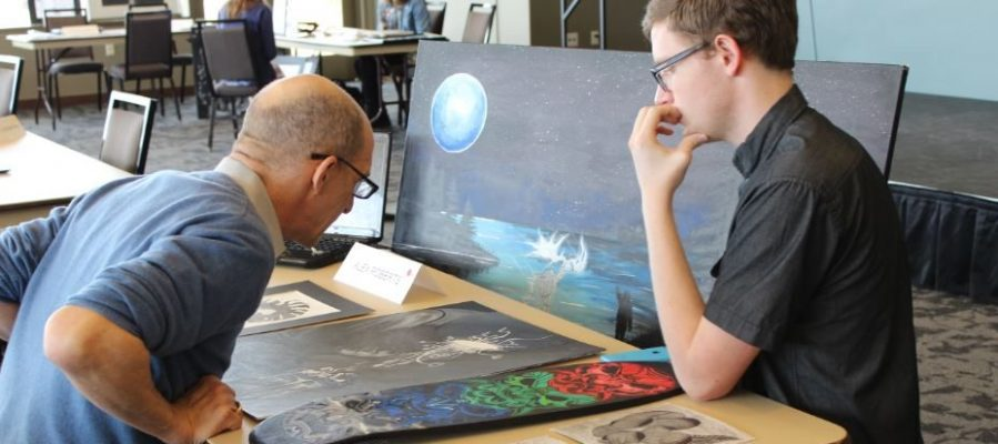 Young artist has his art portfolio critiqued by older artist