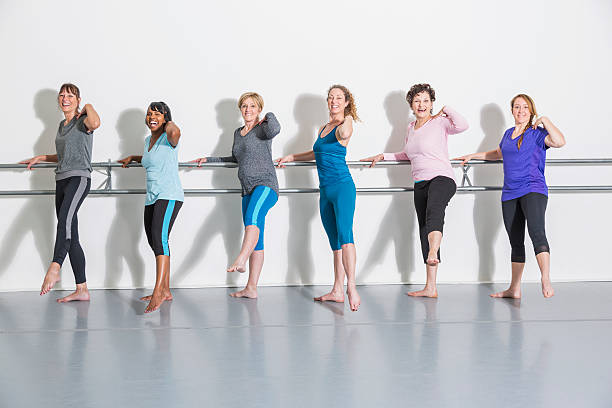 Multi-ethnic group of women doing barre exercises in dance studio.