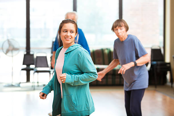 Young Hispanic woman watches the instructor in dance class at local gym. A senior couple is dancing behind her. They are in the exercise studio at the gym. Large bright windows are behind them.