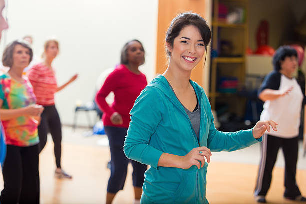 Caucasian dance instructor teaches group of active senior women to line dance. The women are having fun as they learn.