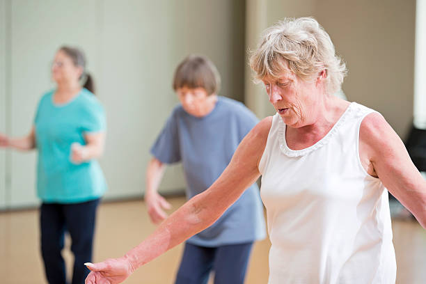 A group of senior women enjoy themselves as they learn to line dance. They are enrolledin a class at their senior center.