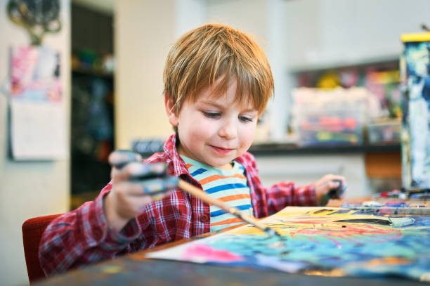 Cute happy little boy, adorable preschooler, painting in a sunny art studio. Young artist at work.