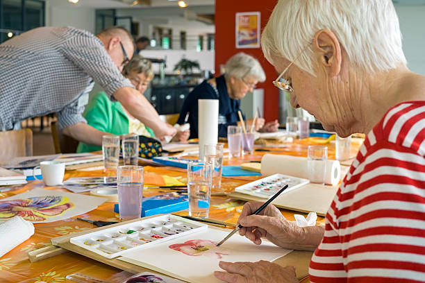 Adult Artwatercolor painting at table with other students in spacious studio.